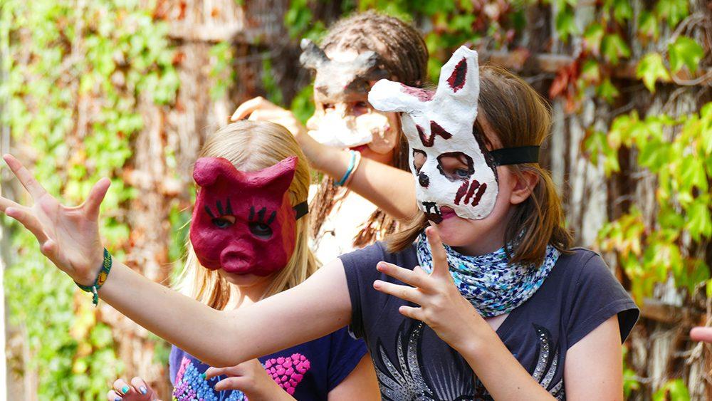 Drei Kinder mit Masken.