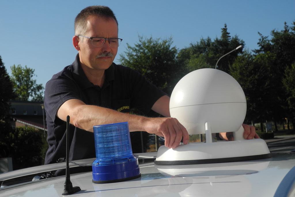 Leiter der Funkwerkstatt bei der Feuerwehr Paderborn montiert Sirene auf Fahrzeugdach.
