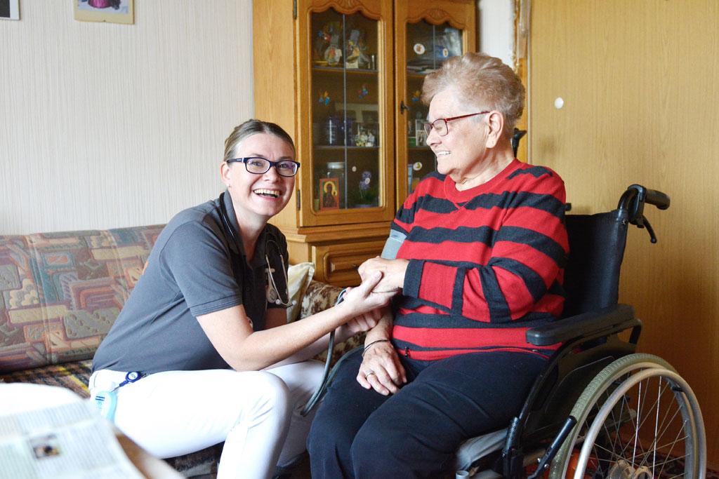Pflegerin hält die Hand einer im Rollstuhl sitzenden Frau.