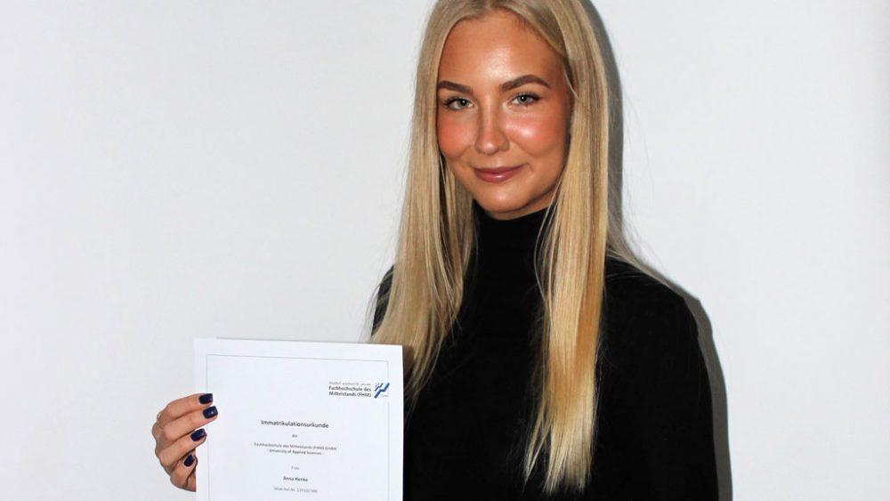 Frau mit Diplom in der Hand.